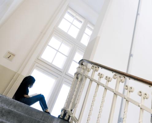 Jongere zit alleen in een trappenhuis